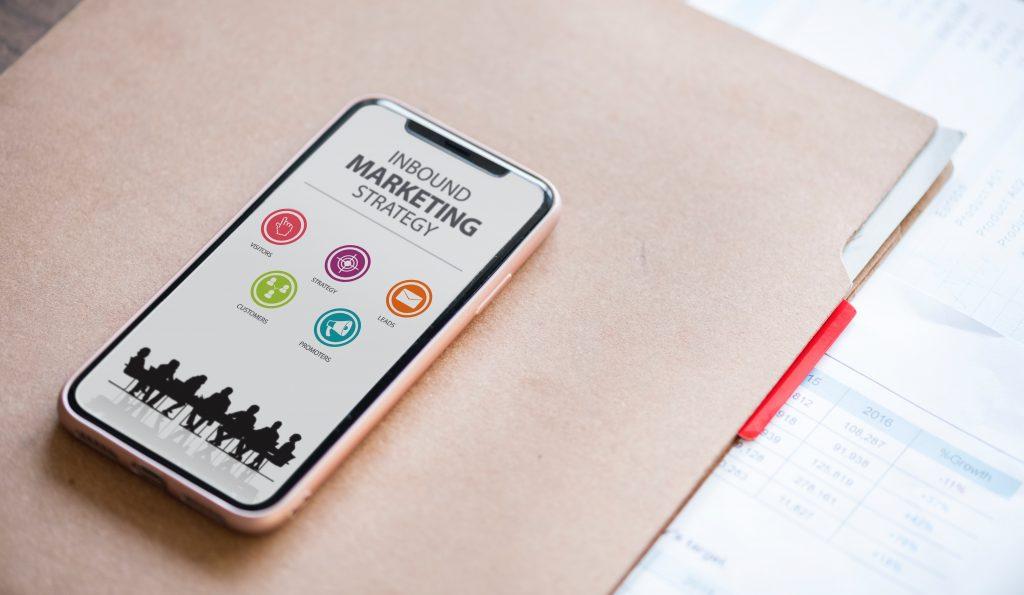 Téléphone posé sur un bureau avec plusieurs stratégies inbound marketing qui s'affichent à l'écran.