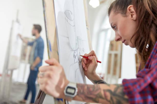 Jeune femme en train de dessiner dans une école d'art