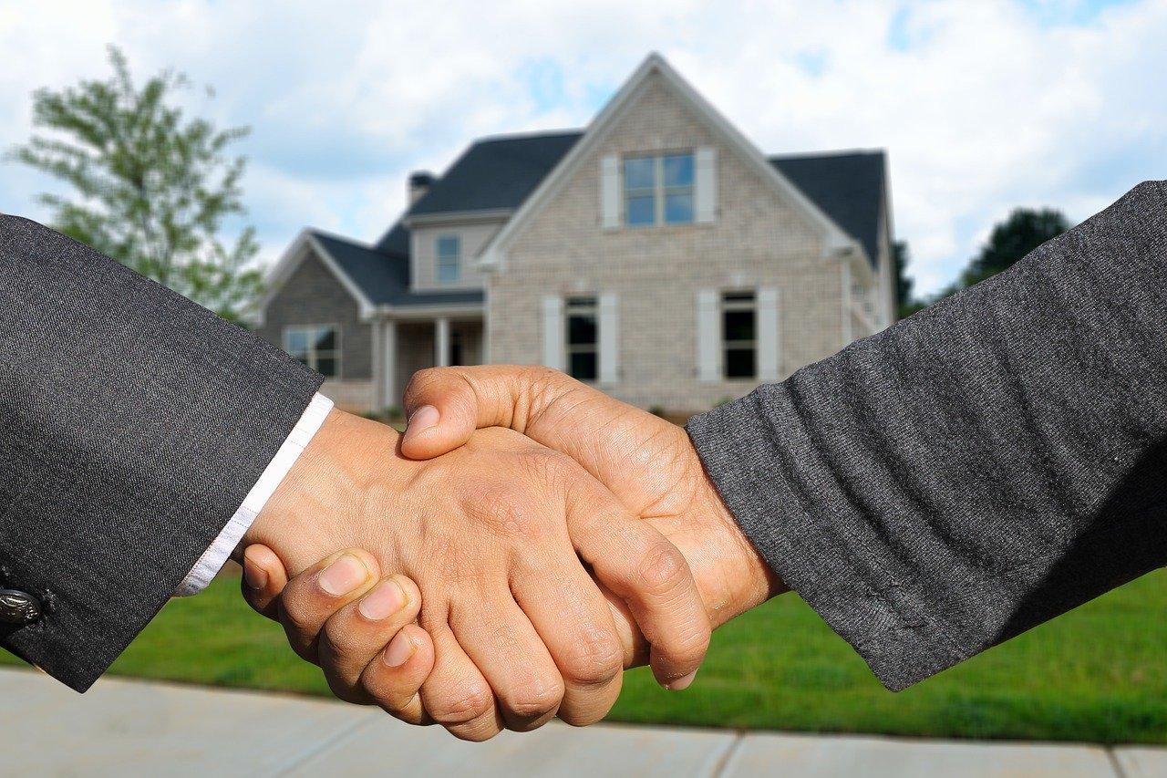 deux personnes se serrent la main devant une maison