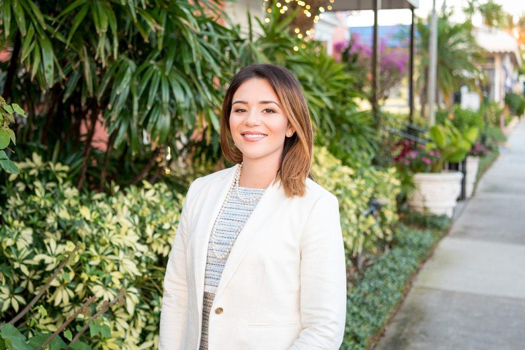 jeune femme, habillée de manière professionnelle, souriant à la caméra