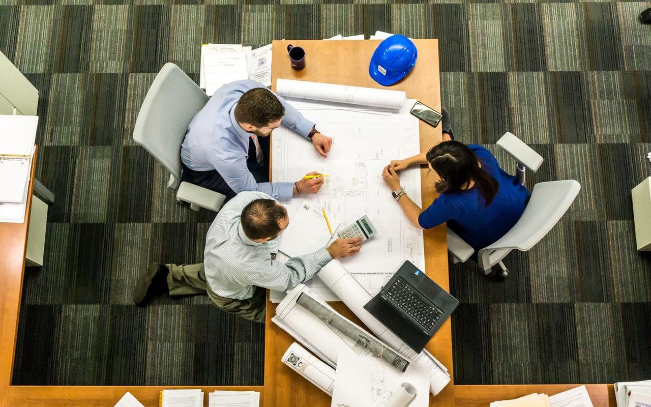 trois personnes travaillant sur le même bureau
