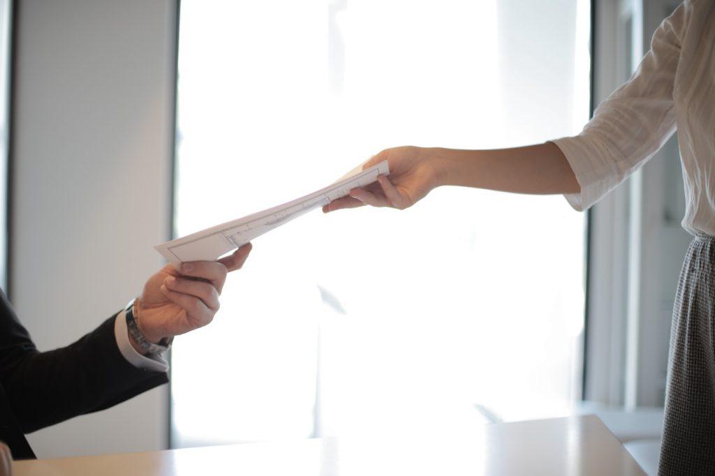 personne qui donne un document à une autre personne en costume