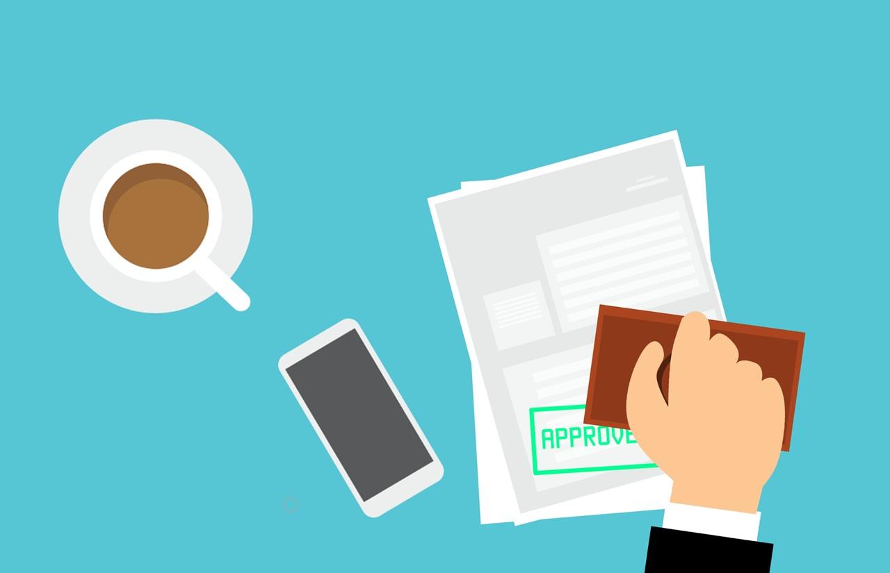 """personne qui approuve un document posé à côté d""""un smartphone et d'une tasse à café"""